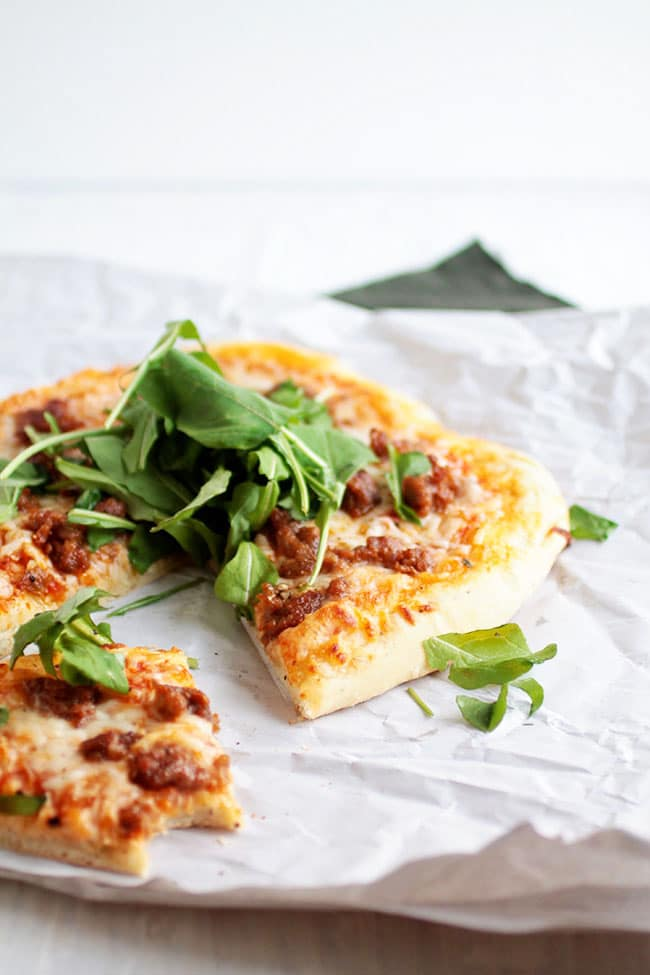 Small pizza topped with fresh arugula, with one slice removed.