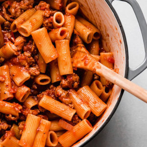 Wooden spoon stirring rigatoni and tomato sauce in a light grey pot