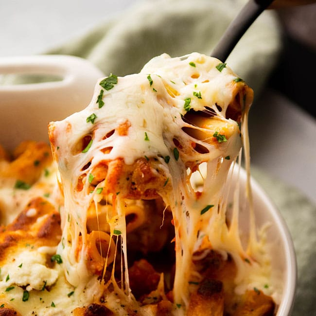 Spoon lifting baked ziti out of a white baking dish