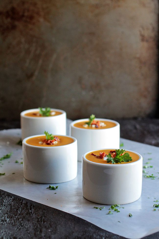 Four small white bowls filled with butternut squash soup.