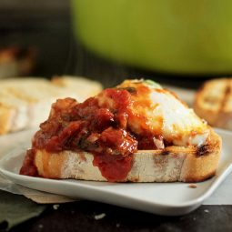 Sourdough toast topped with a baked egg and tomato sauce.