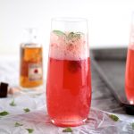 Pink Bourbon Spritzer, served in a champagne glass with a fresh basil sprig.