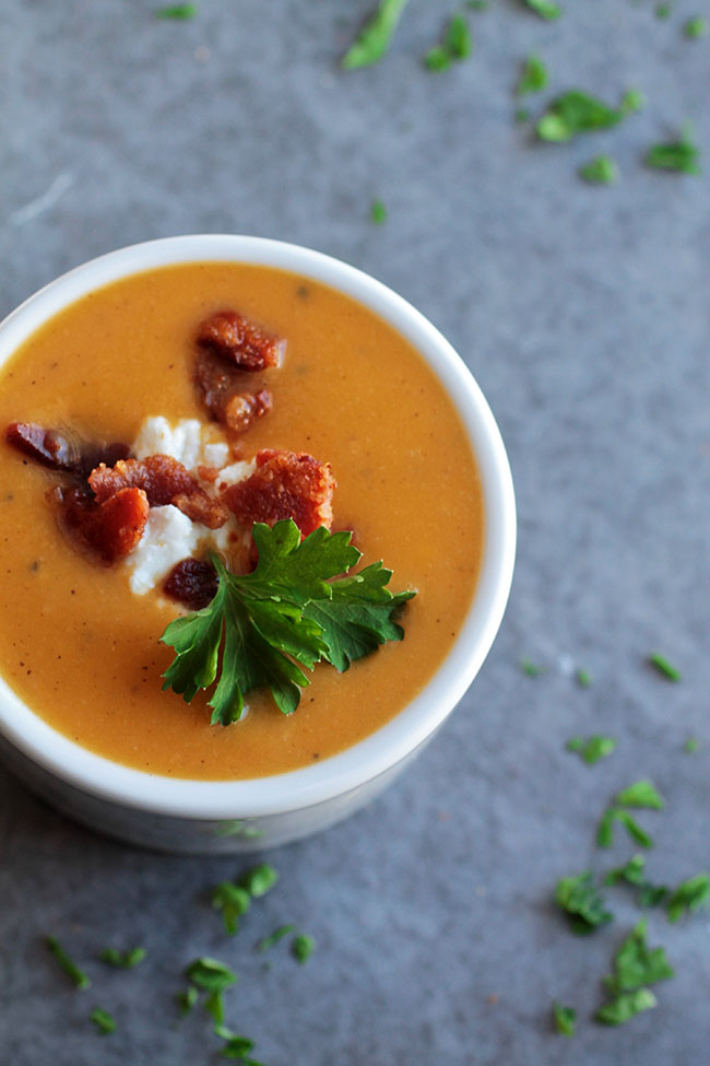 Butternut squash soup in a white bowl, topped with bacon, crumbled goat cheese, and fresh parsley.