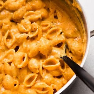 Black spoon stirring shell pasta with butternut squash sauce in a large pot