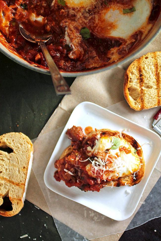 Toast, tomato sauce, and a baked egg on a white plate next to a large pot of baked eggs.