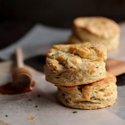 Two biscuits in a stack next to a honey dipper.