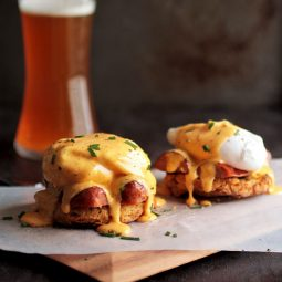 Eggs benedict on a wood serving board in front of a dark background.