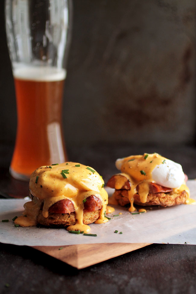 Eggs benedict on a wooden serving board in front of a tall glass of beer.