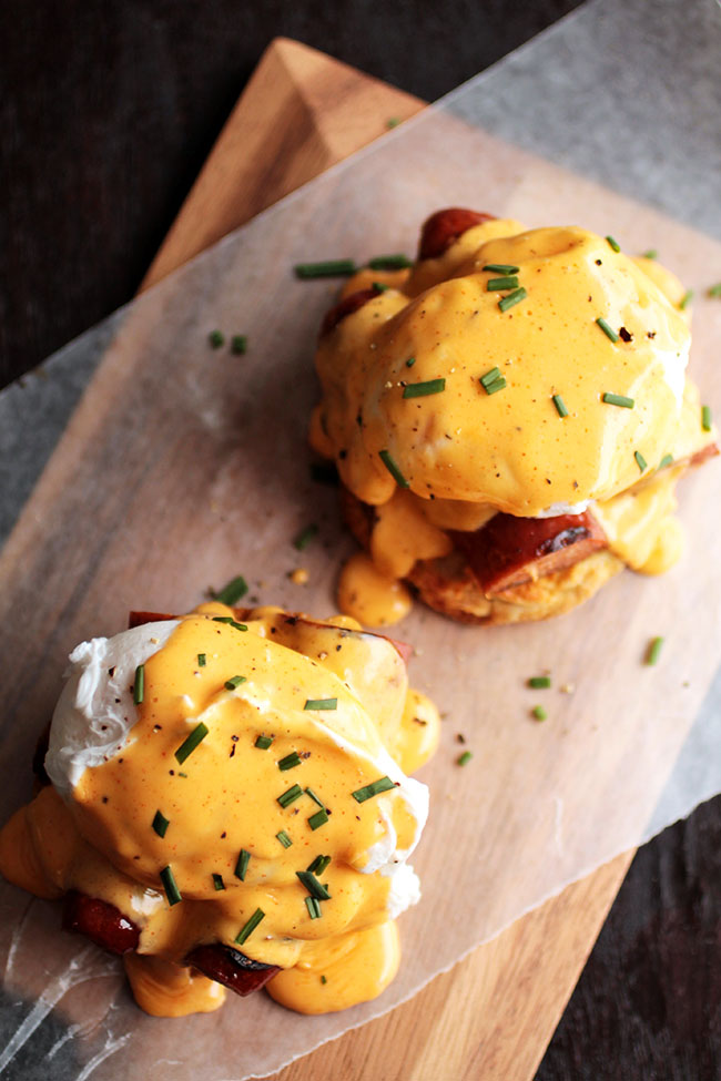 Eggs benedict on a wooden serving board.