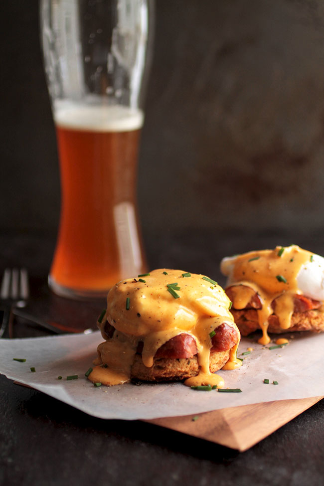 Eggs benedict on a white plate next to a tall glass of beer.