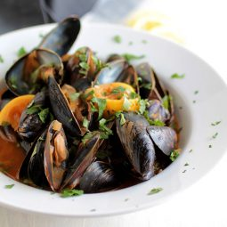 Mussels, lemon wedges, and chipotle sauce in a shallow white bowl.