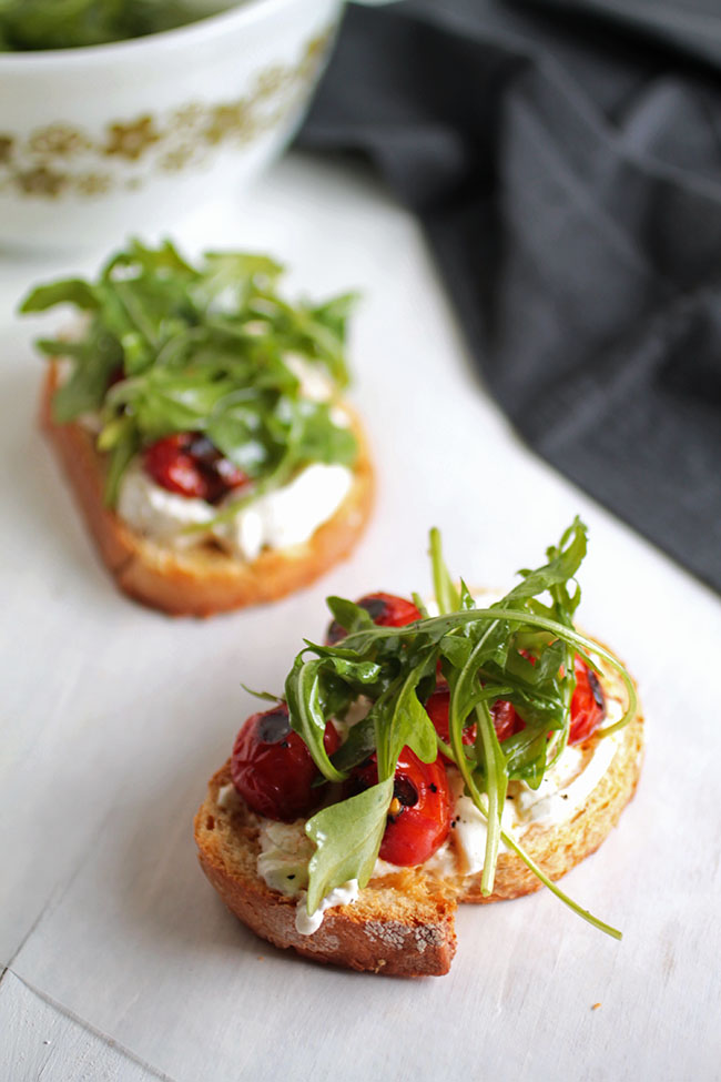 Need some new ideas for crostini toppings? Try this fresh arugula and blistered tomato combo with creamy burrata! Vegetarian.