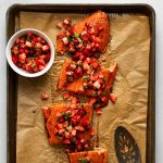 Salmon fillet topped with strawberry salsa on a baking sheet lined with brown parchment paper