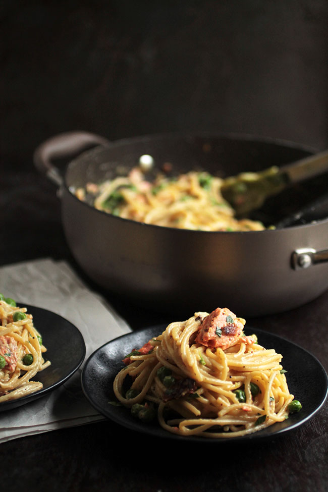 Simple salmon pasta with spring peas, candied bacon, and an easy carbonara sauce.