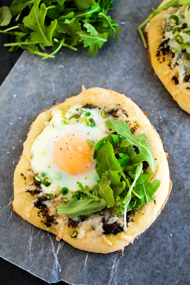 Spring Veggie Breakfast Pizzas - This easy recipe for breakfast pizza is sure to be a hit! Fresh spring vegetables, plenty of cheese, and an egg on top. Vegetarian.