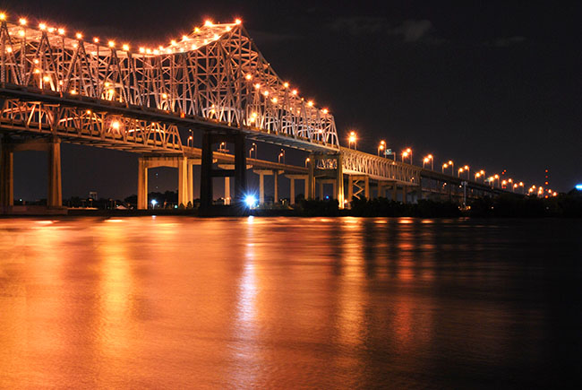 A New Orleans bridge, lit up at night.