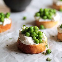 Several crostini on a table lined with white butcher paper.