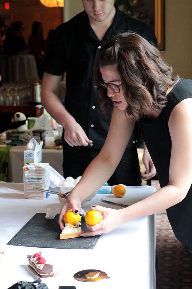 Molly Yeh arranging a slice of cake on a serving platter during a photography demonstration.
