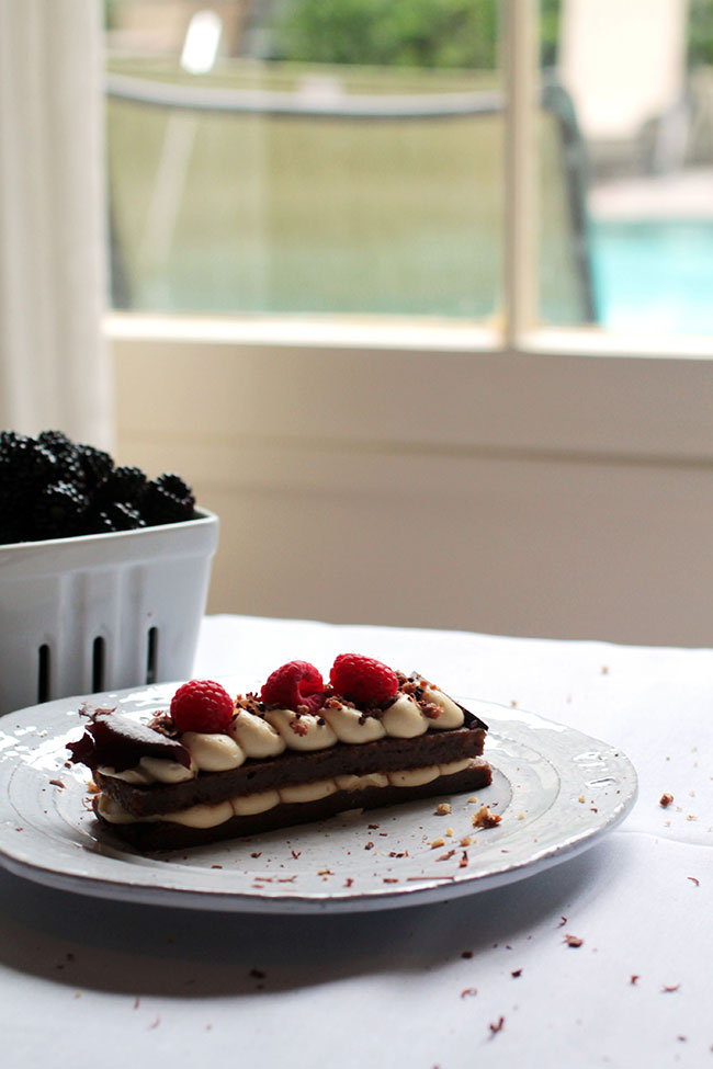 Slice of cake on a white plate in front of a window.