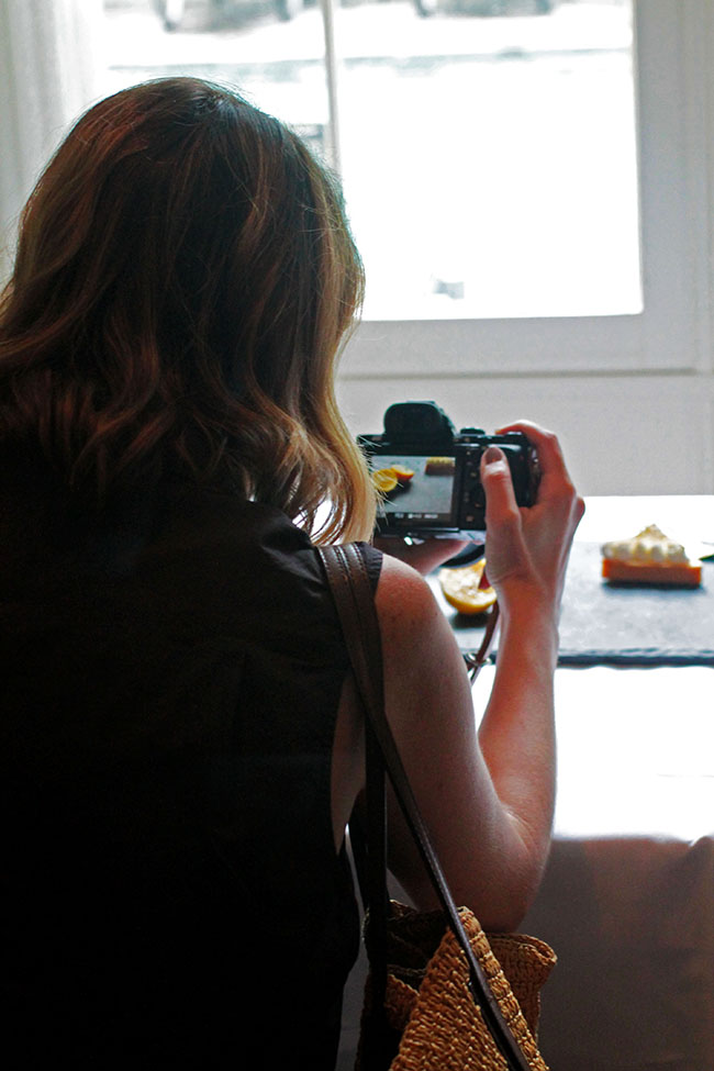 Woman taking a photo of a piece of cake.