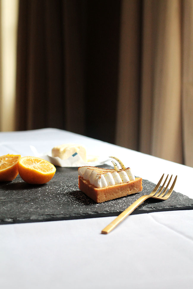 A piece of cake on a dark serving platter with a gold fork.