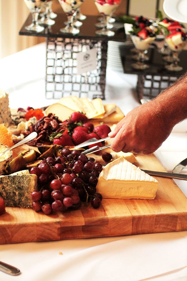 Hands using tongs to take a slice of cheese from a wooden cheese board.
