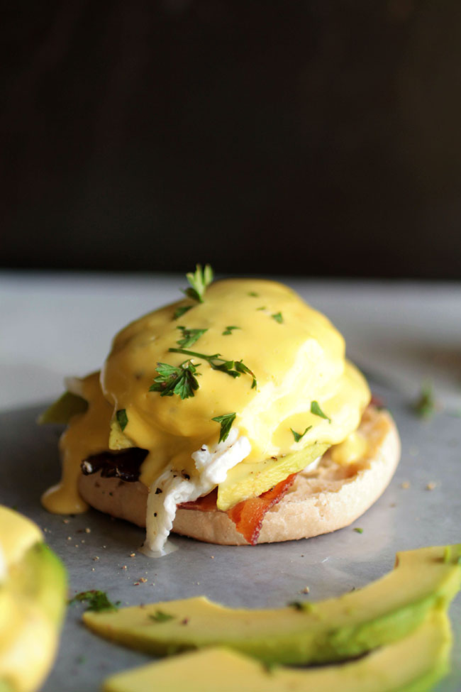 Eggs benedict topped with fresh parsley.