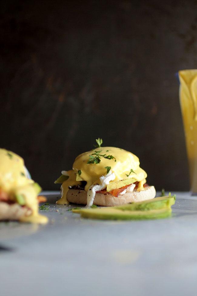 Eggs benedict next to fresh avocado slices.