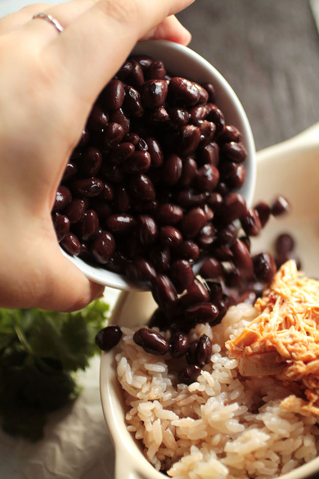 Hands pouring black beans into a burrito bowl.