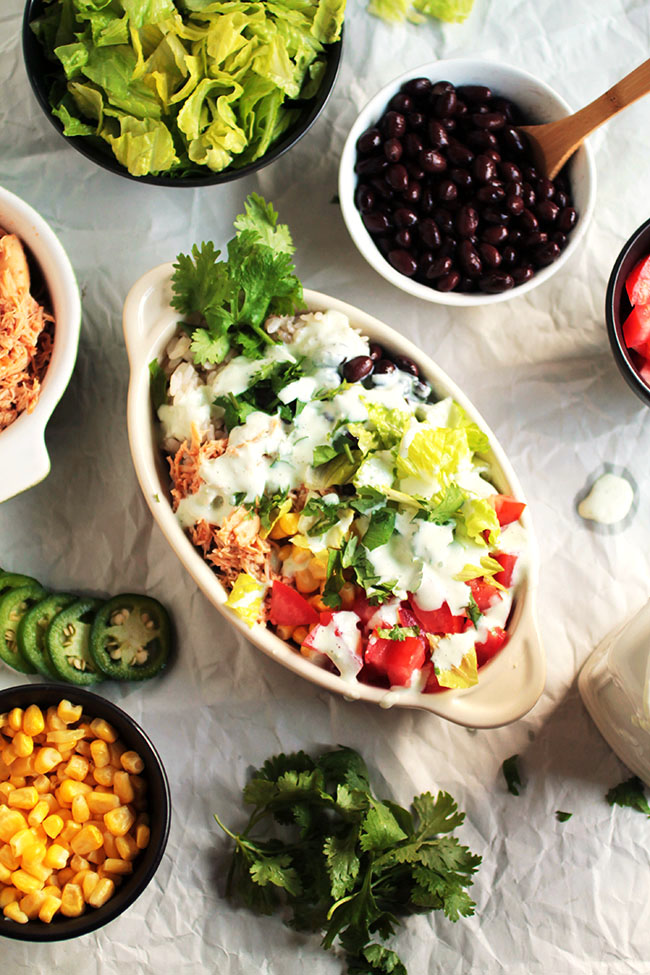 A burrito bowl in a tan serving dish, surrounded by small bowls of ingredients.