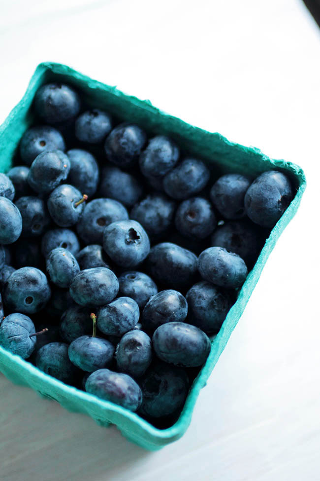 Green produce container filled with blueberries on a white surface.