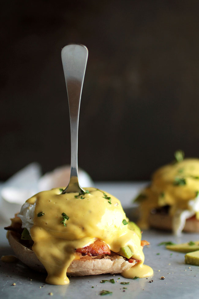 A small fork stuck into the center of a poached egg in eggs benedict.