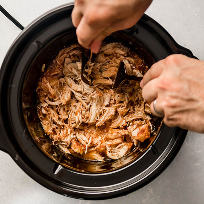 Man's hands shredding chicken in a black crock pot