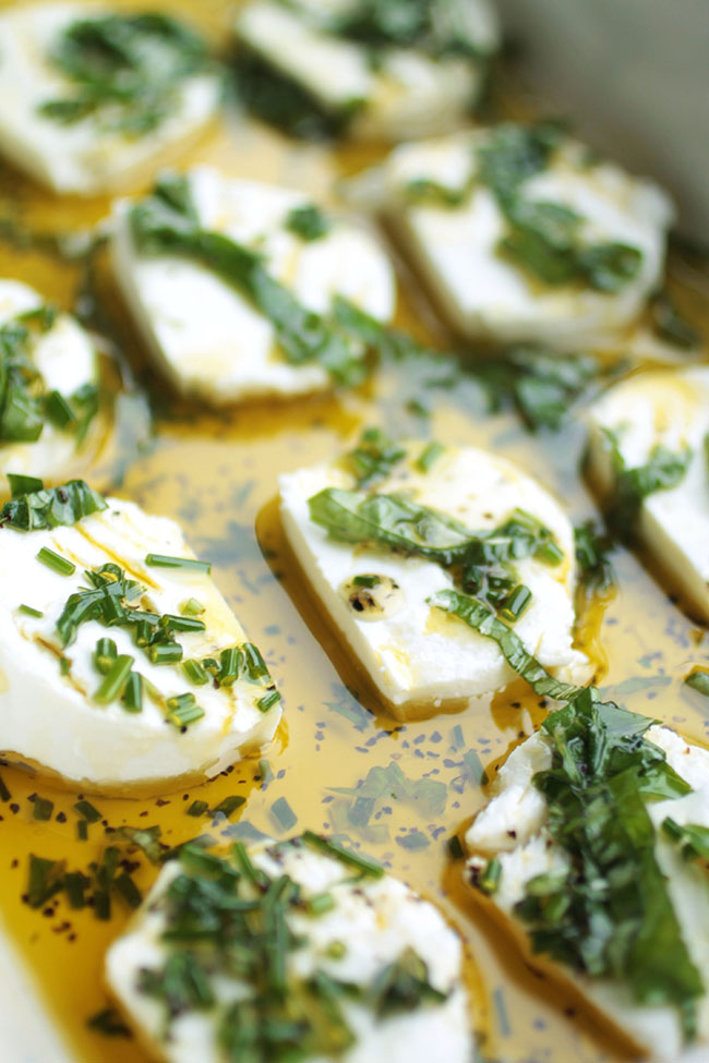 Goat cheese rounds in a dish with olive oil and herbs.