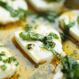 Close up of a goat cheese round in olive oil, topped with fresh herbs.