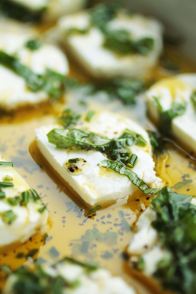 Sliced goat cheese in a baking dish with olive oil and fresh herbs.