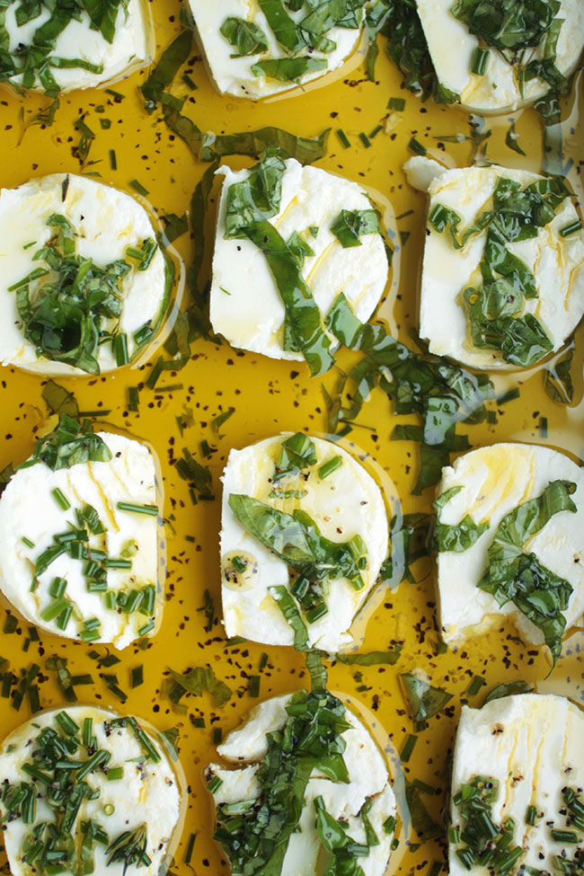 Sliced goat cheese in a baking dish with olive oil and chopped herbs.