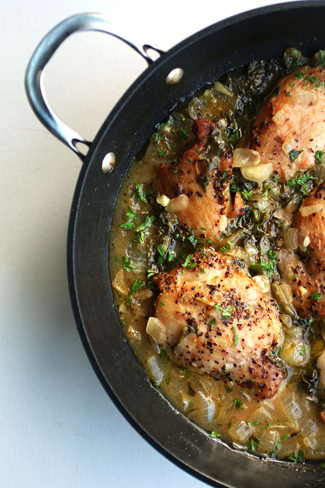 Overhead photo of cooked chicken thighs in a large saucepan