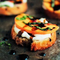 Peach bruschetta topped with fresh basil and balsamic drizzle.