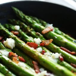 Asparagus in a cast iron skillet with blue cheese and crumbled bacon.