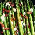 Bright green asparagus spears topped with crumbled bacon and blue cheese.