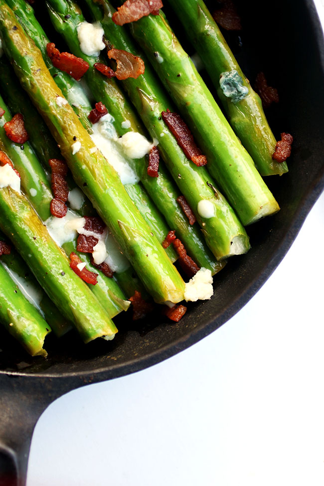Asparagus spears on a cast iron skillet with blue cheese and bacon.