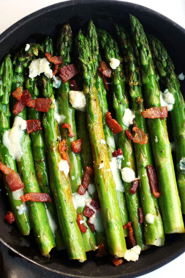 Close up of asparagus topped with bacon and blue cheese.