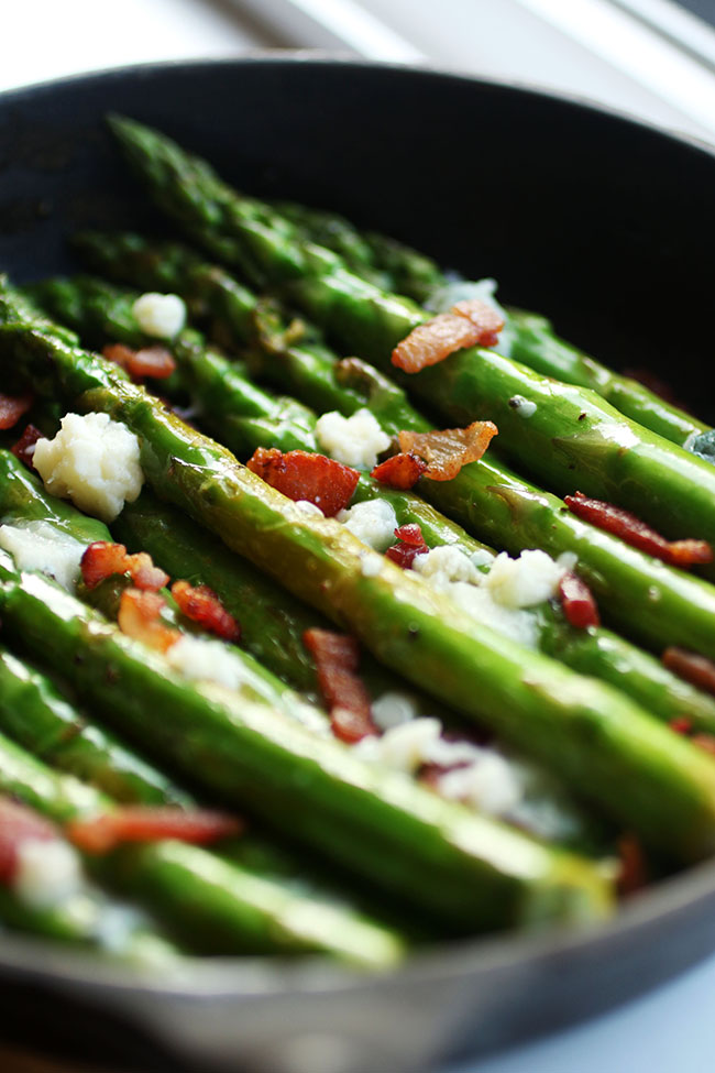 Close up of asparagus in a skillet with bacon and blue cheese.