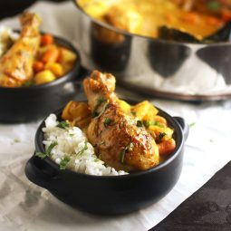Curry chicken in a small black dish with white rice.