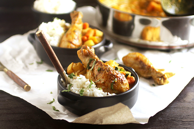 Chicken curry and white rice in shallow black bowls.
