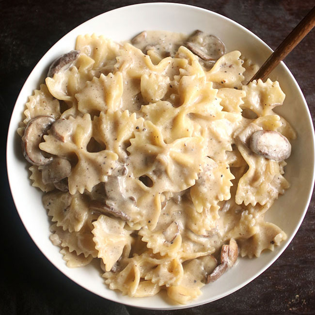 overhead photo of bowtie pasta with creamy mushroom pasta sauce in a shallow white bowl on a brown background