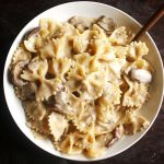 overhead photo of a white bowl filled with bowtie pasta and mushroom sauce on a dark brown table