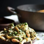 Fettuccine with peas and shrimp on a dark wooden plate.