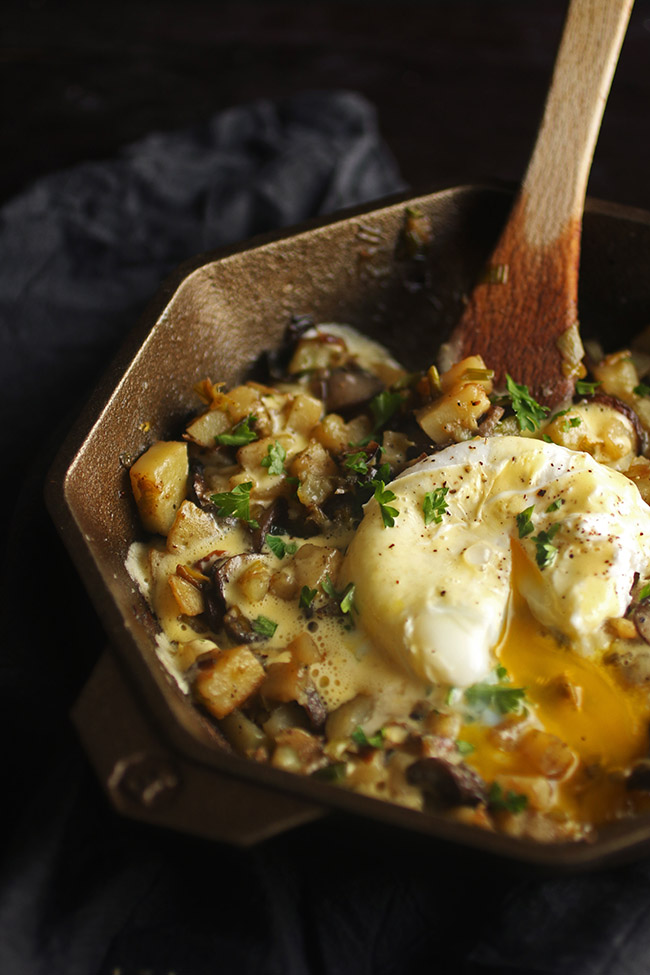 Cast iron skillet filled with breakfast hash and topped with a poached egg and hollandaise sauce
